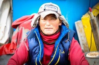 Korean fisherman at Busan fish market dressed in red with a hat to keep warm in the winter weather. Busan, South Korea
