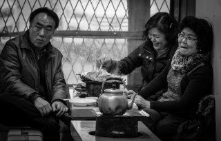 Environmental street portrait of friends enjoying steaming hot pot lunch, taken on a bitterly cold day at Busan fish market