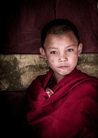Portrait of a novice monk in his red robes at a Bhutan monastery
