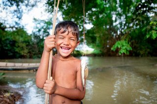 Portrait of young bot catching a fish by Graeme Heckels Travel Photography
