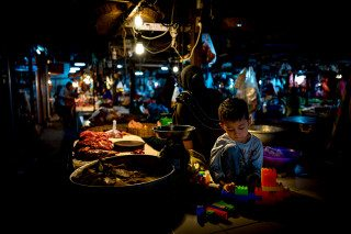 Boy playing with toys in Siem Reap Meat Market by Graeme Heckels Travel Photography Cambodia