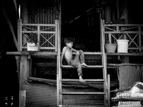Portrait of a boy in Siem Reap floating village by Graeme Heckels Travel Photography