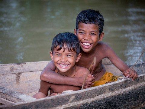 Portrait of brothers playing on a boat in Siem Reap by Graeme Heckels Travel Photography