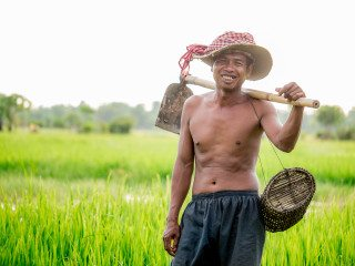 Portrait of Farmer working in paddy field by Graeme Heckels Travel Photography