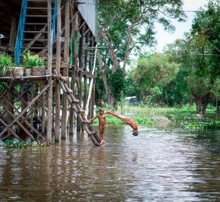 Boys play in water at Tonle Sap by Graeme Heckels Travel Photography