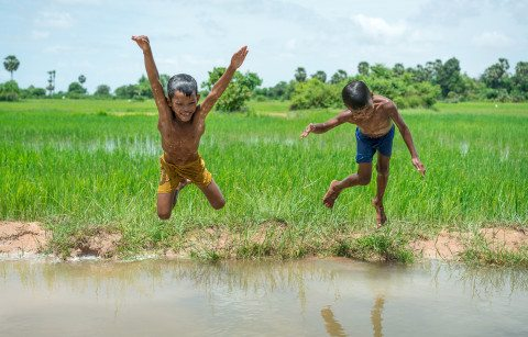 Two boys jump into river in Siem Reap Countryside by Graeme Heckels Travel Photography