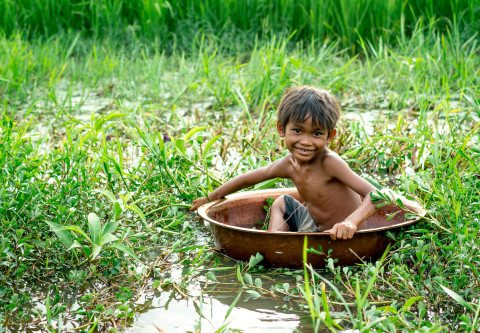 Cute boy plays in bowl in Siem Reap Rice Paddy Field Graeme Heckels Travel Photography