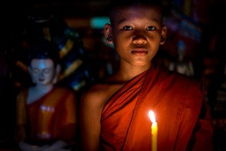 Novice Monk meditates by candle in Siem Reap Temple by Graeme Heckels Travel Photography