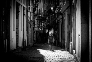 Candid smoker walking in the laneways of Porto by Graeme Heckels Travel & Street Photography