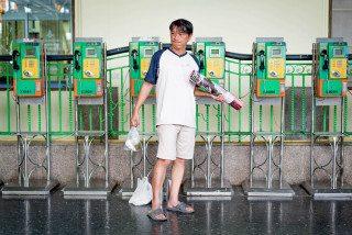 Candid man at phone boxes at Hua Lumphong Station Bangkok by Graeme Heckels Street & Travel Photography