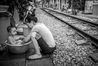 Black and White photo by Graeme Heckels Hanoi Street Photography Life on The Train Tracks Baby Bathtime