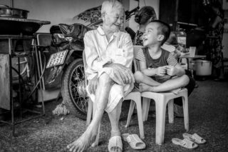 Black and White photo by Graeme Heckels Hanoi Street Photography Generations Grandfather Grandchild Family Portrait