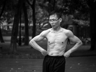 Black and White photo by Graeme Heckels Hanoi Street Photography Strong Man